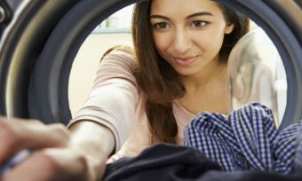 Women putting clothes in dryer