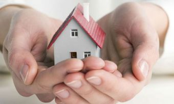 Person holding miniature house
